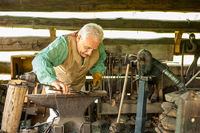 Artisan works in the woodworking shop at Mountain Farm Museum