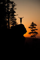 Silhoutte of a young woman posing on a rocky cliff against a colorful sunset