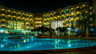 Night time photo of a swimming pool at a tropical resort or hotel