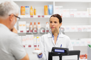 apothecary showing drug to senior man at pharmacy