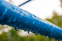 Raindrops on a blue metal pipe