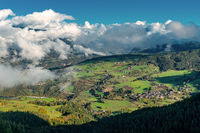 View onto the village of Ums , Voels am Schlern, up in the italian Alps on a sunny day with dense white clouds thriving over the valley