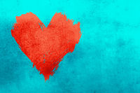 Red watercolor painted heart shape over blue