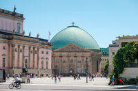 People at historic district (Bebelplatz) of Berlin in font of the State Opera building and St. Hedwig's Cathedral