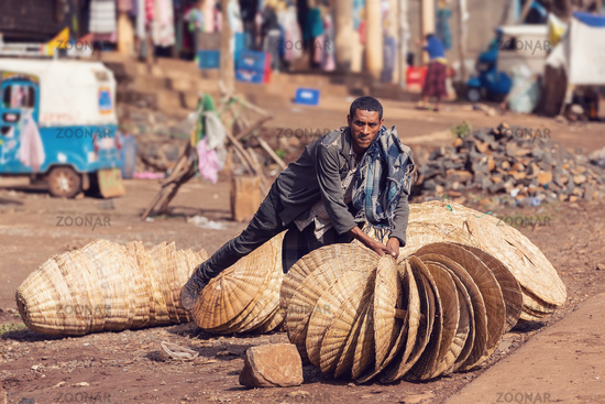 Ethiopian man sells wicker baskets on the street