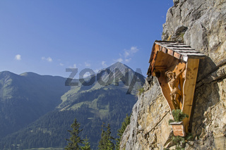 Kruzifix aus Holz an steiler Felswand