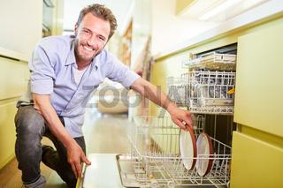 Mann räumt Geschirrspüler in Küche aus