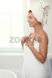 Hübsche junge Frau steht in ihrem Badezimmer