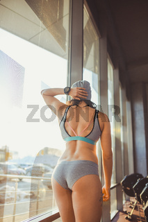 Female fitness model in top posing near big window. fitness model have break after workout. Confident athletic woman with sixpack abs posing. Fitness model posing in gym equipment blurred background
