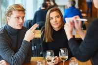 Junges Paar bestellt Essen beim Kellner im Restaurant