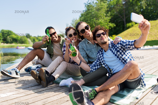 friends with drinks taking selfie by smartphone