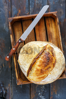 Loaf of artisanal sourdough bread and a knife.