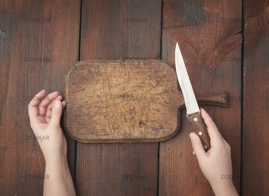 very old empty wooden rectangular cutting board and hands hold a sharp knife