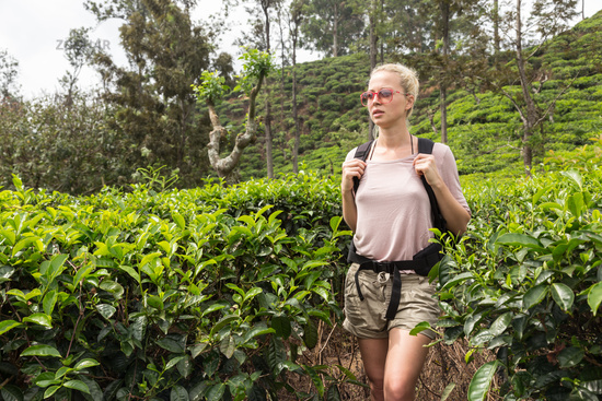 Active caucasian blonde woman enjoing fresh air and pristine nature while tracking among tea plantaitons near Ella, Sri Lanka. Bacpecking outdoors tourist adventure