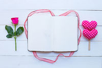 Diary notebook with rose and valentine's hearts on white wooden background.