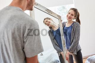 Junges Paar transportiert gemeinsam einen Spiegel