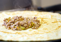 Frying pancake stuffed by meat and greenery on pan