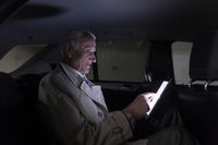 Businessman with a digital tablet sitting in the back seat of a car