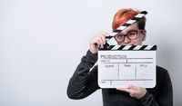 redhead woman holding movie  clapper on white background