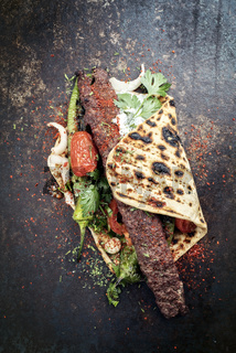 Traditional Adana kebap on a skewer with tomato and yogurt on a flatbread