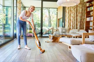 Hausfrau reinigt Parkett Boden im Wohnzimmer