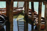 Rowing boats under wooden footbridge, Pragser Wildsee, Pragser Dolomiten, South Tyrol, Italy.