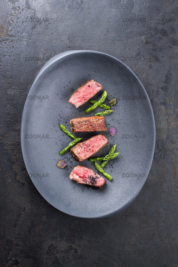 Barbecue dry aged wagyu fillet steak with blanched green asparagus tips and herbs as top view on a modern design plate with copy space