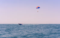 Sea view of a man Parasailing in the water towed by a speedboat in American flag colours - Watersports summer sports concept