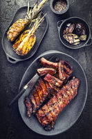 Barbecue spare ribs St Louis cut hot honey chili marinade with pineapples and eggplant as top view on a modern design cast iron pan