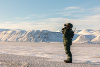 Man in arctic landscape. Person standing with a rifle and binoculars, watching the arctic landscape at Svalbard