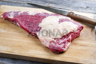 Raw dry aged wagyu tri trip steak as closeup on a wooden board
