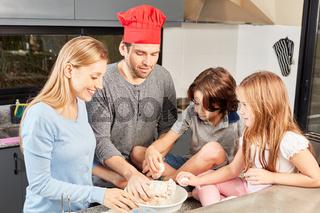 Familie mit zwei Kindern beim Brot backen