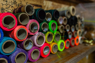Colorful threads on a shelf in workshop