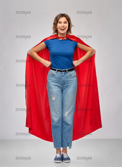 happy woman in red superhero cape