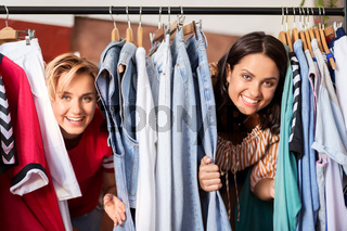 women having fun at vintage clothing store hanger