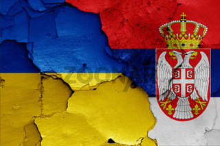 flags of Ukraine and Serbia painted on cracked wall