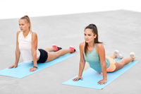 women doing sports on exercise mats outdoors