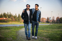 Two handsome young men, friends, in a park