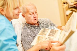 Senior Mann mit Demenz betrachtet Fotoalbum