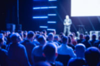 Crowd of seated business people in the background of the presenter on stage. Defocused blurred picture for background