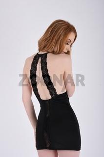Ashley Foxx, sexy, vollbusige Rothaarige in einem engen schwarzen Minikleid