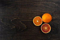 A closeup photo of vibrant organic blood oranges on a dark background with copy space.