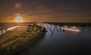 Luftaufnahme eines Kreuzfahrtschiffes auf der Elbe in Fahrt bei Sonnenuntergang