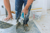 Worker in uses grinder for cutting tiles porcelain stoneware work