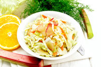 Salad of cabbage and rhubarb in plate on white wooden board