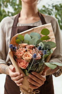 Young girl hold fresh natural floral bouquet with roses, eryngium and green leaves. Concept of Mother's Day.