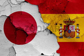 flags of Japan and Spain painted on cracked wall