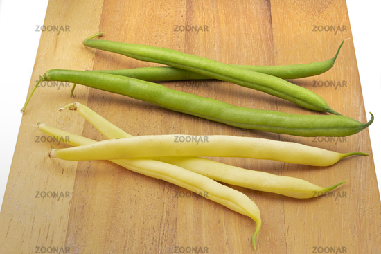 Green and yellow beans on wooden boards