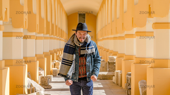 Portrait of a stylish handsome young man with a scarf outdoors.  A happy man wearing a scarf, hat and a denim jacket laughing