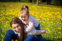 Young girl and her mom playing on meadow, family time, summer day, blurred background